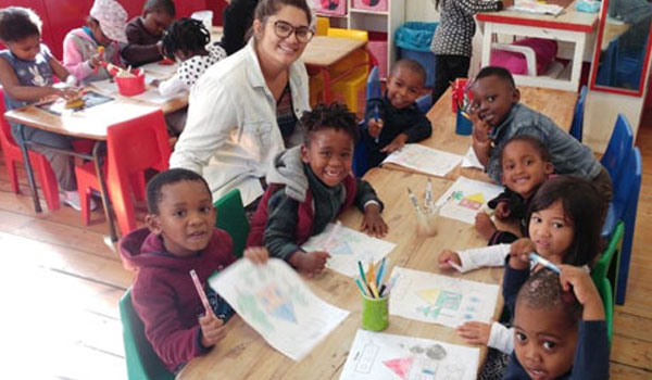 Happy volunteer teaching kids to draw